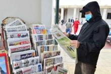 lector con mascarilla leyendo un diario en la calle