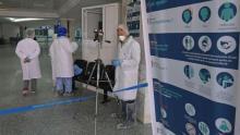 personal médico con trajes especiales a la entrada de un hospital marroquí